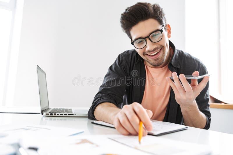 Glad stilig man i glasögon som talar, genom smartphonen och att arbeta royaltyfria foton