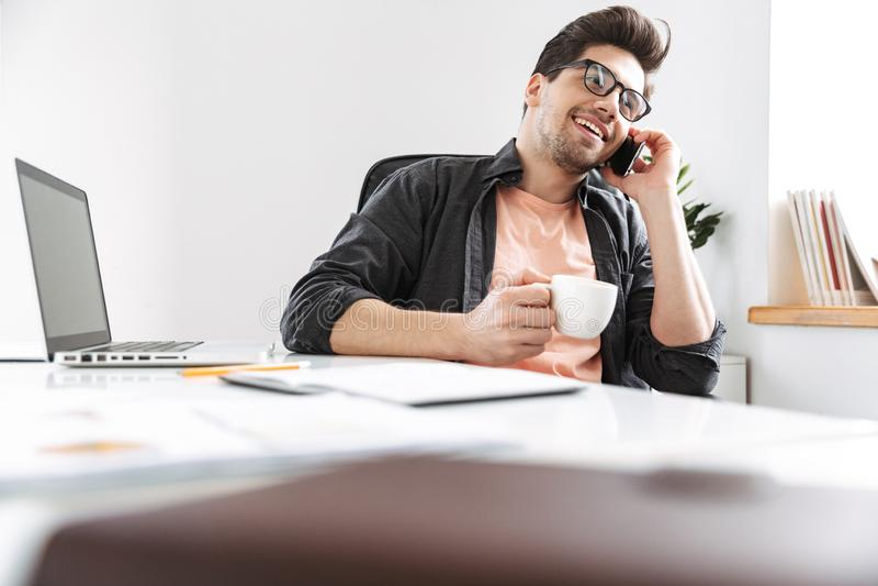 Glad stilig man i glasögon som talar vid smartphonen royaltyfria bilder