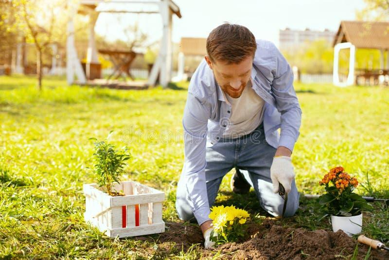 Glad stilig man som sätter blommor in i jordningen arkivbild
