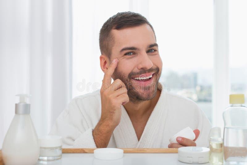 Glad stilig man som sätter kräm på hans framsida arkivfoto