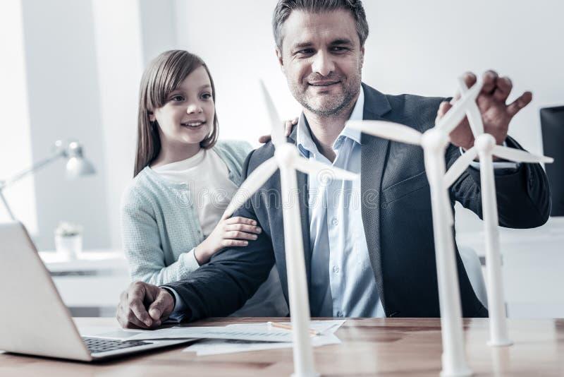 Glad tekniker som berättar hans dotter om alternativ energi royaltyfri fotografi