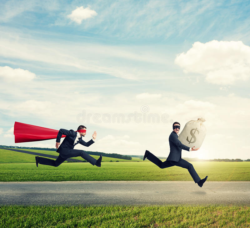Glad thief and superman stock photo