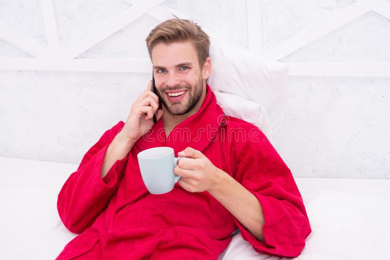 Glad to hear. Mobile conversation. Mobile call. Communication mobile phone. Good news concept. Good morning. Hipster guy stock image
