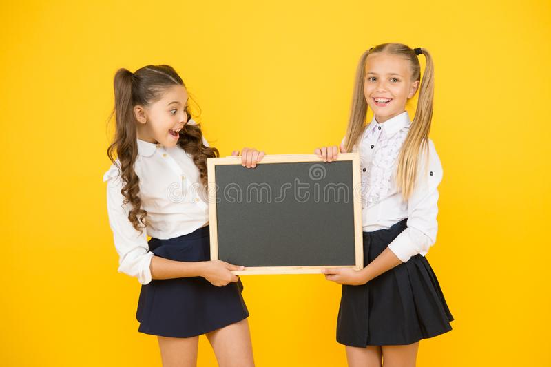 Glad to inform. Schoolgirls informing you. School girls hold blank chalkboard copy space. Girls school uniform hold. Blackboard. Back to school concept royalty free stock images