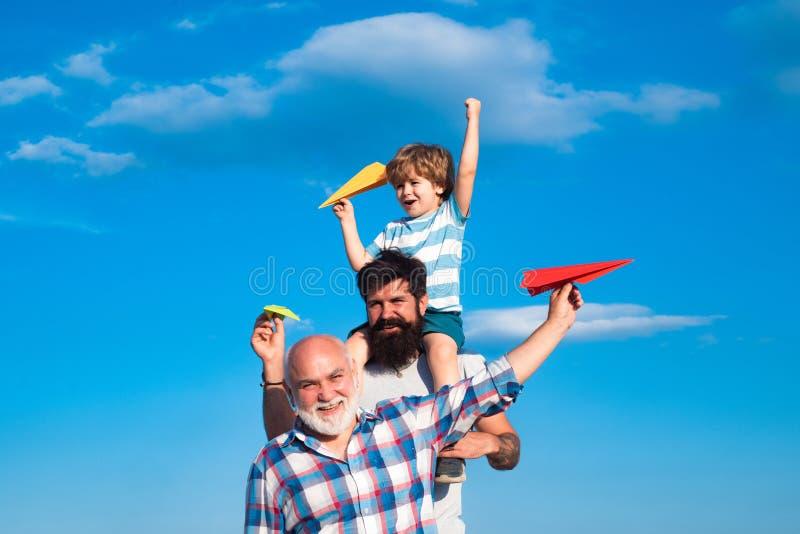 Glad tre generationer män har kul och leende på blå himmelsbakgrund. fader som leker utomhus sonen. flygplan arkivfoton