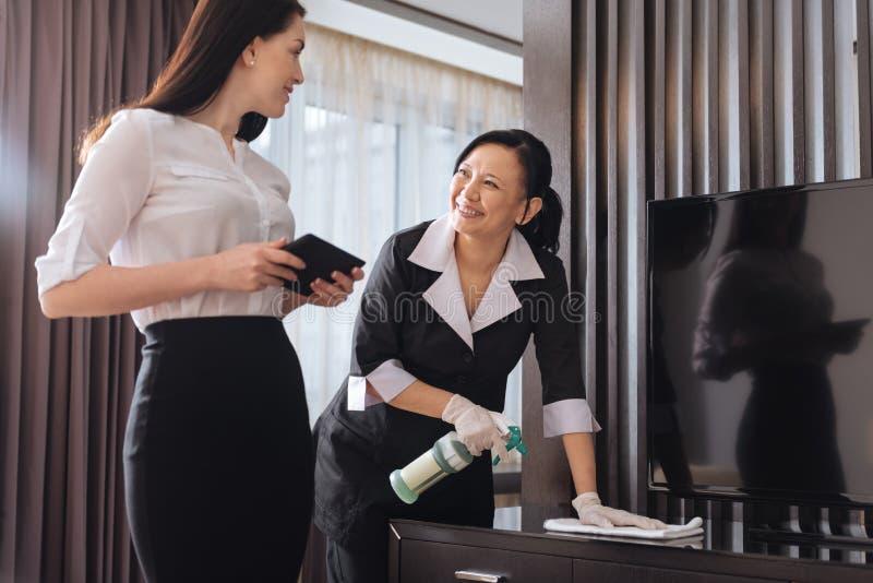 Glad trevlig affärskvinna som talar till en hotellhembiträde fotografering för bildbyråer