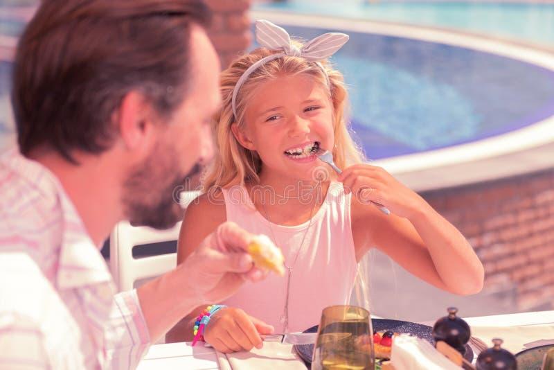 Glad trevlig flicka som sätter mat i hennes mun royaltyfria foton
