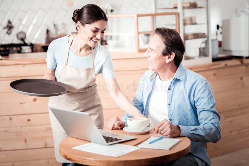 Glad trevlig kvinna som sätter en kopp kaffe på tabellen arkivfoto