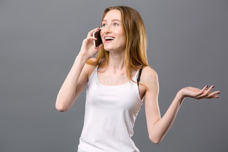 Glad trevlig kvinna som sätter en telefon till hennes öra arkivbilder