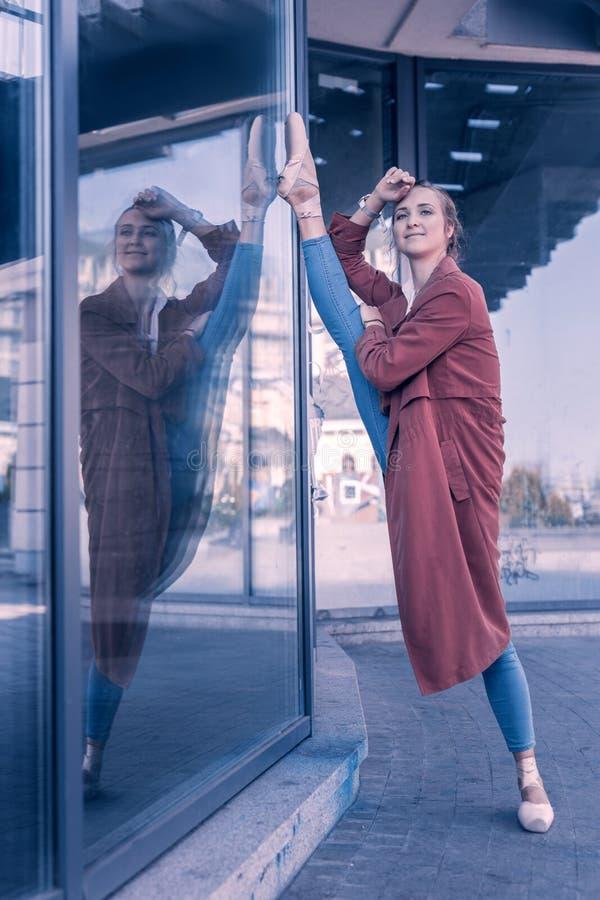 Glad trevlig kvinna som sätter hennes ben på den glass dörren royaltyfri foto
