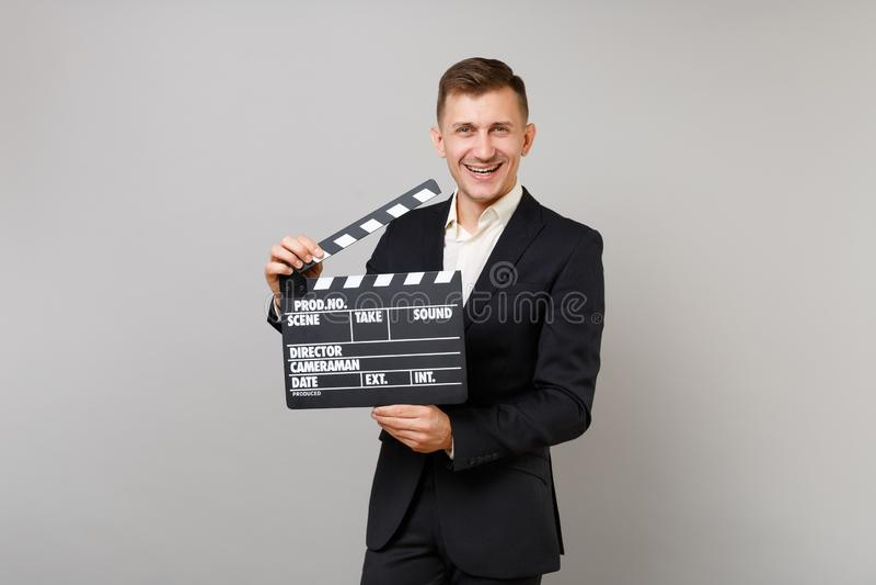 Glad ung affärsman i den klassiska svarta dräkten, skjorta som rymmer den klassiska svarta filmen som gör clapperboard som isoler arkivbild