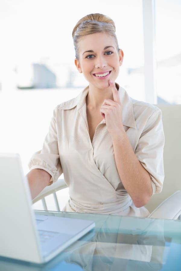 Glad ung blond affärskvinna som använder en bärbar dator royaltyfri bild
