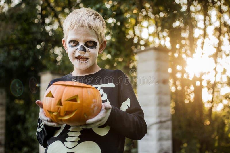 Glad ung, blond hårpojke med skelettstumma som håller i ett gänge Halloween Försök eller behandla Porträtt utomhus arkivbilder