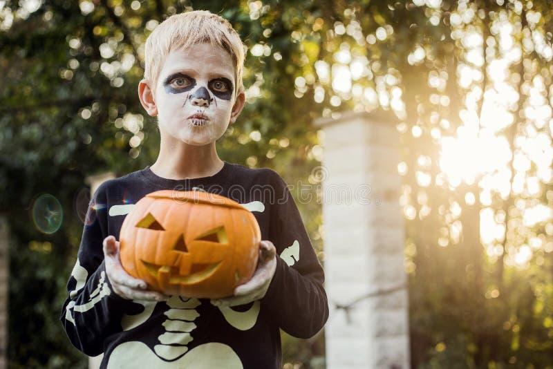 Glad ung, blond hårpojke med skelettstumma som håller i ett gänge Halloween Försök eller behandla Porträtt utomhus arkivbild