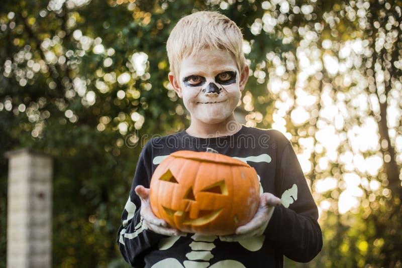 Glad ung, blond hårpojke med skelettstumma som håller i ett gänge Halloween Försök eller behandla Porträtt utomhus royaltyfria foton