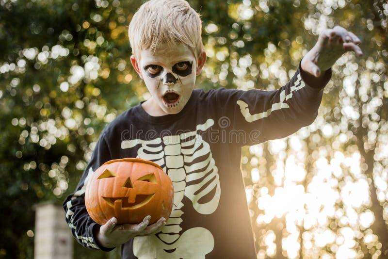 Glad ung, blond hårpojke med skelettstumma som håller i ett gänge Halloween Försök eller behandla Porträtt utomhus royaltyfri foto