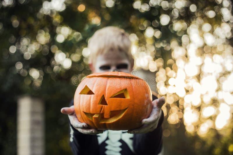 Glad ung, blond hårpojke med skelettstumma som håller i ett gänge Halloween Försök eller behandla Porträtt utomhus arkivfoto