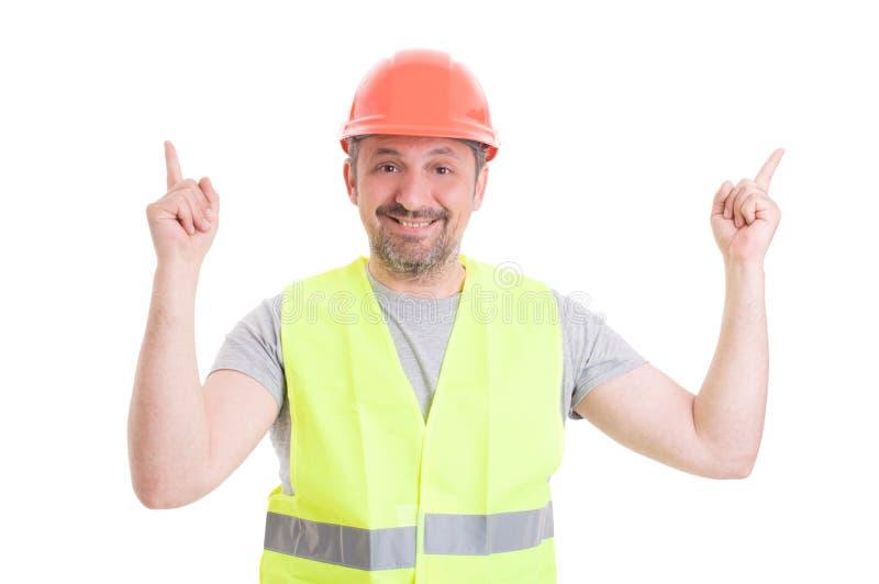 Glad ung byggmästare som pekar fingrar till vit copyspace royaltyfria foton