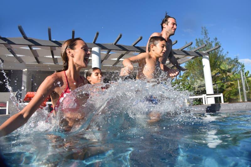 Glad ung familj som hoppar till simbassängen royaltyfri fotografi