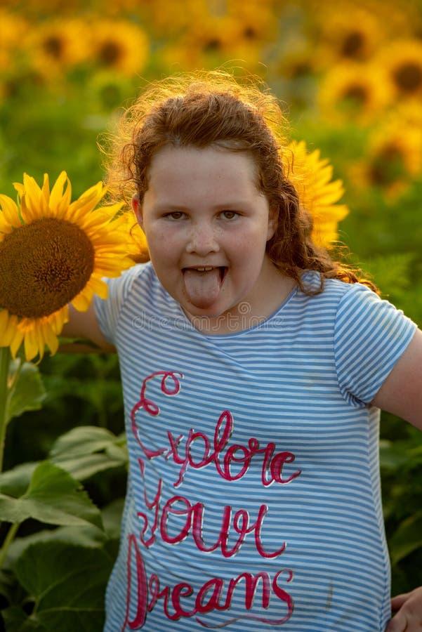 Glad ung flicka för skönhet med solrosen som tycker om naturen och skrattar på sommarsolrosfält Sunflare solstrålar, glöd arkivbild