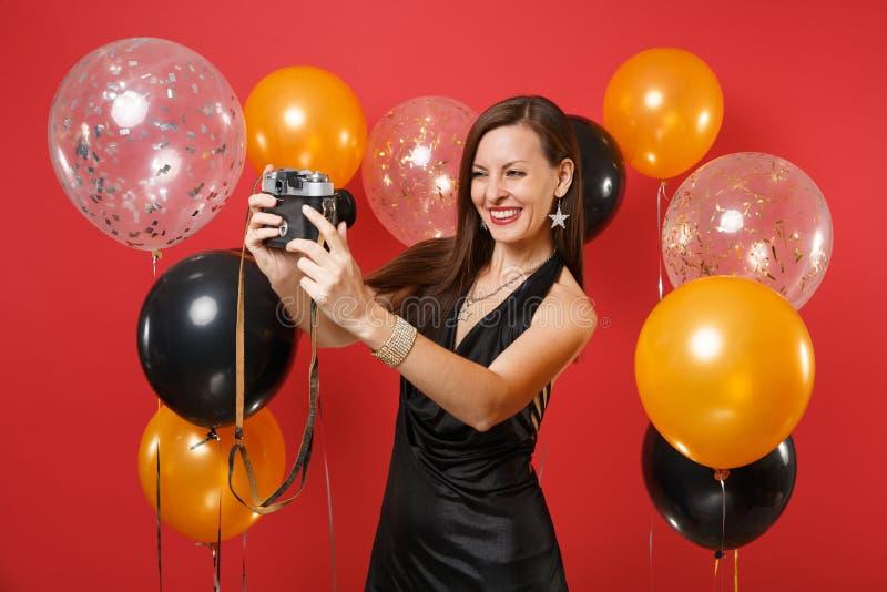 Glad ung flicka i den lilla svarta klänningen som gör ta selfie som skjutas på retro tappningfotokamera på ljus röd bakgrund royaltyfria foton