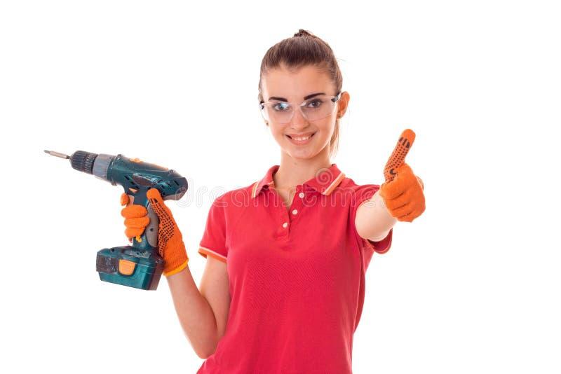 Glad ung flicka i en röd t-skjorta och genomskinliga skyddande exponeringsglasshower grupp och innehav en drillborr arkivfoton