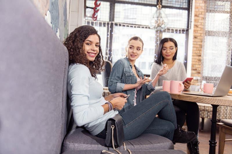 Glad ung kvinna som besöker kafét med vänner arkivfoto