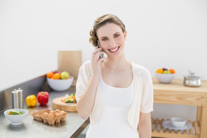 Glad ung kvinna som ringer med hennes smartphoneanseende i kök royaltyfri fotografi