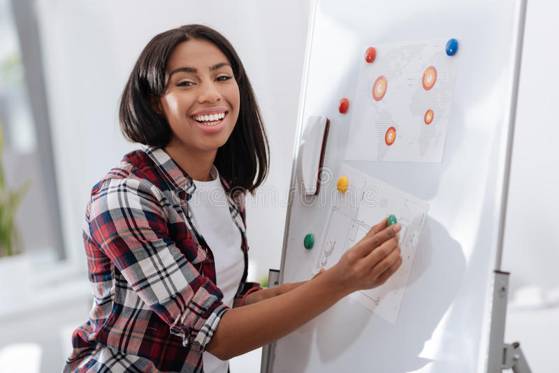 Glad ung kvinna som sätter visuella material på whiteboarden royaltyfri bild