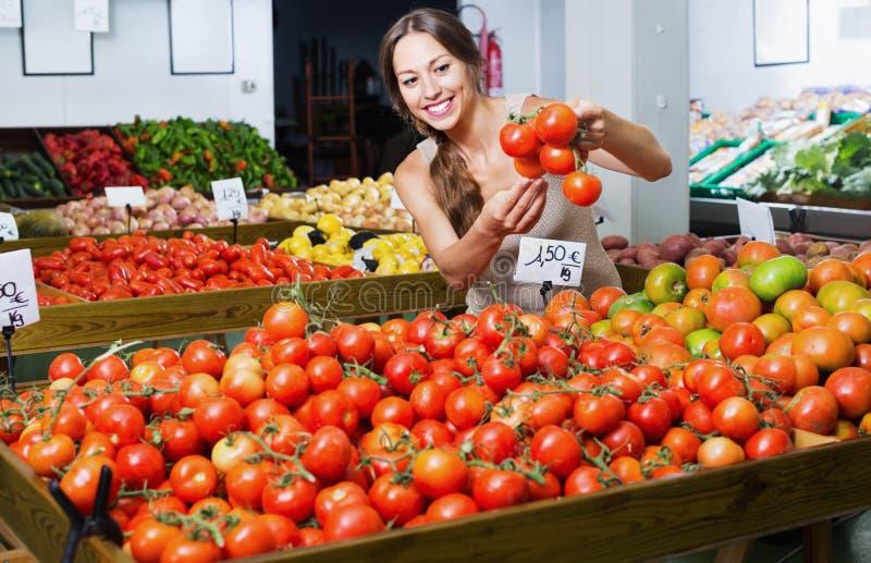Glad ung kvinna som väljer nya tomater arkivbilder