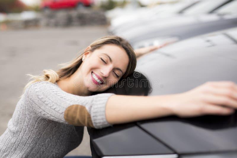 Glad ung kvinnlig chaufför som kramar hennes nya bil fotografering för bildbyråer