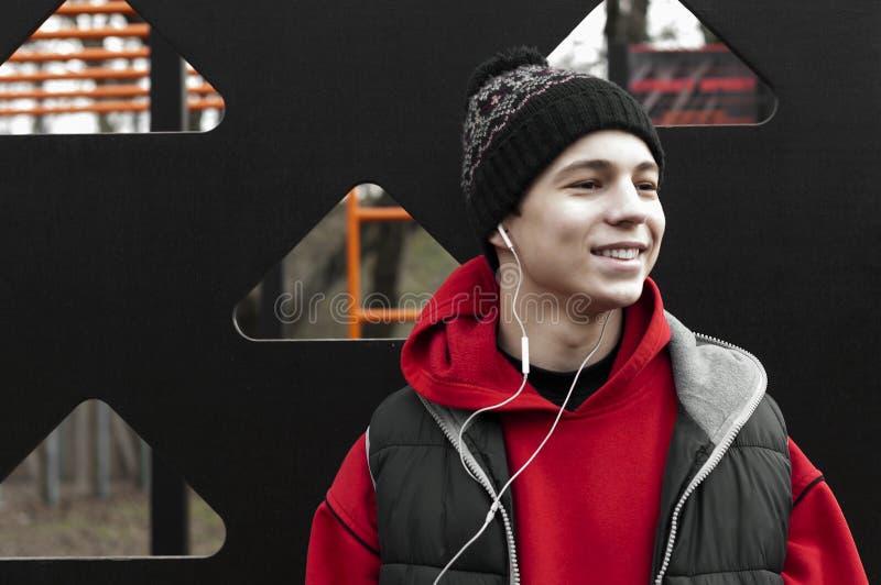 Glad ung man som lyssnar till musik på hörlurar royaltyfri foto
