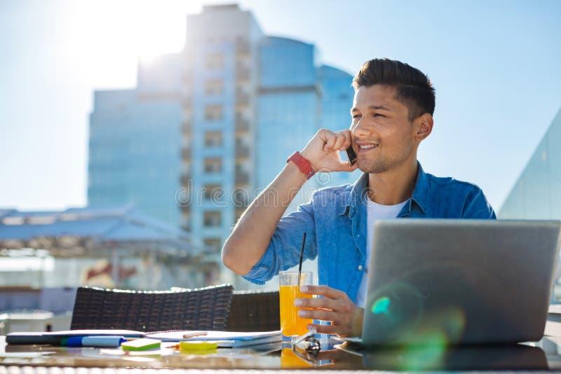 Glad ung man som utomhus talar på telefonen arkivfoto