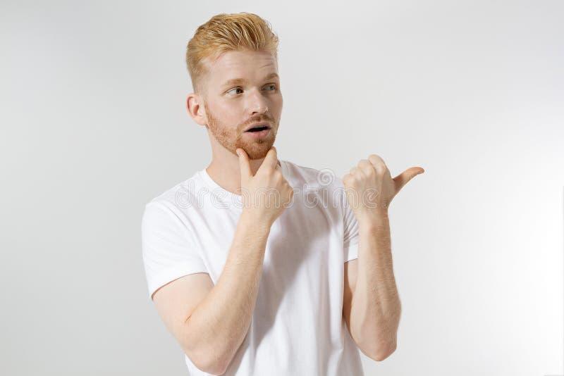 Glad ung rödhårig kille, rött snyggt skägg isolerat Man som pekar på kopieringsutrymme för reklam Manlig i vit t-skjorta, trendhå royaltyfri fotografi