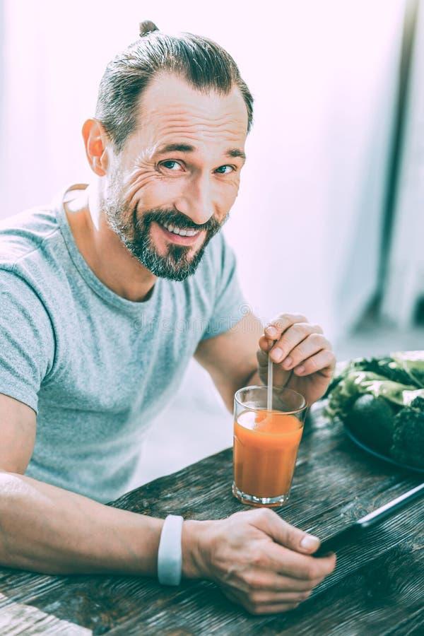 Glad upphetsad man som dricker ny fruktsaft i köket royaltyfria foton