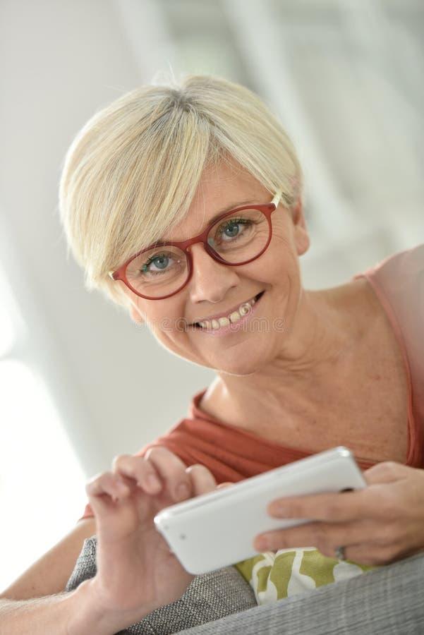Glad utsmyckad hög kvinna med smartphonen arkivbild