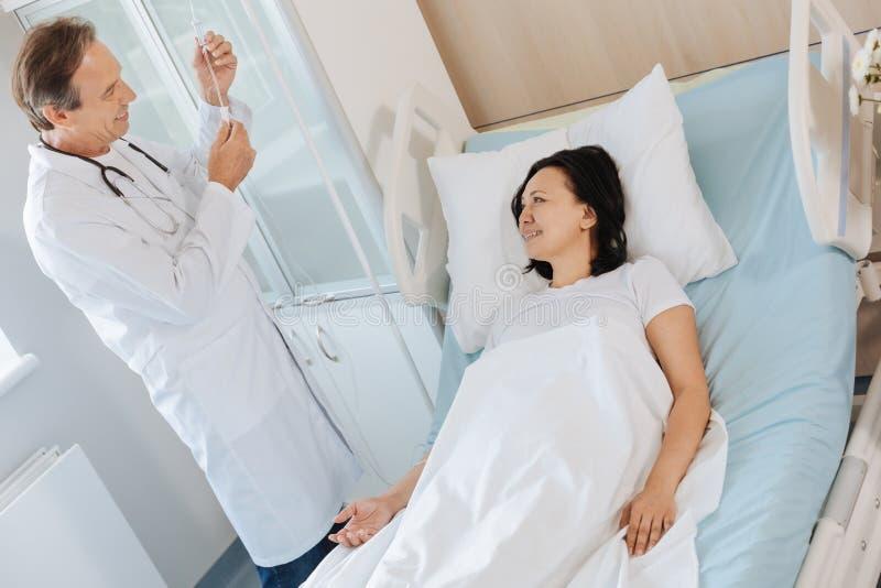 Glad vänlig doktor som talar med hans patient fotografering för bildbyråer