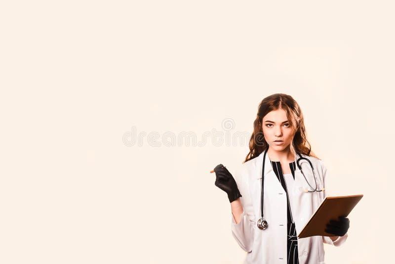 Glad vacker kvinnlig läkare i läkarrock Skriver en medicinsk bakgrund i anteckningsboken med ett fonendoskop svarta handskar royaltyfri fotografi