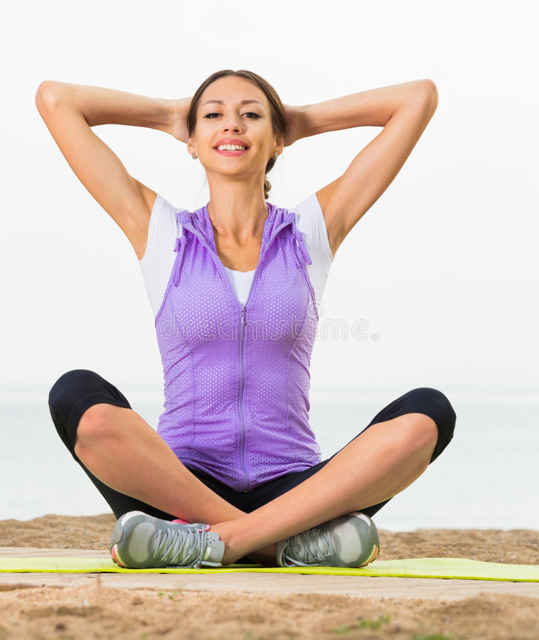 Glad woman practise yoga cross-legged. In morning by sea royalty free stock image