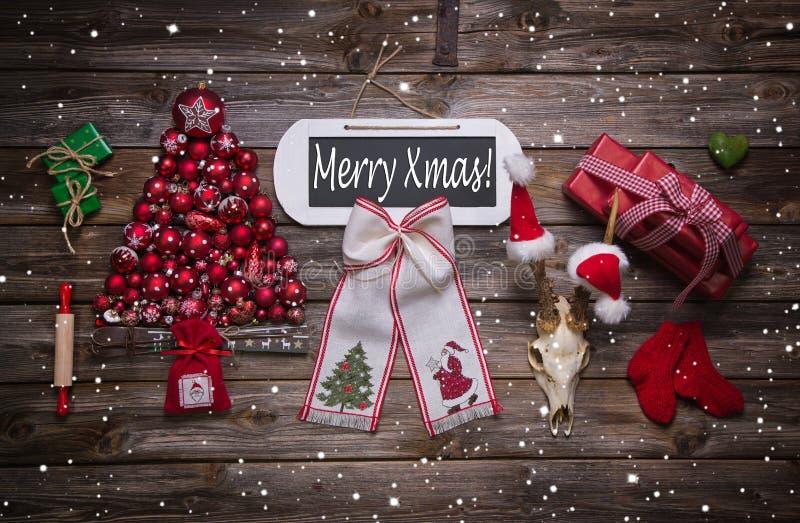 Glad xmas-text på trätecken med klassiska röda julanständigheter royaltyfri foto