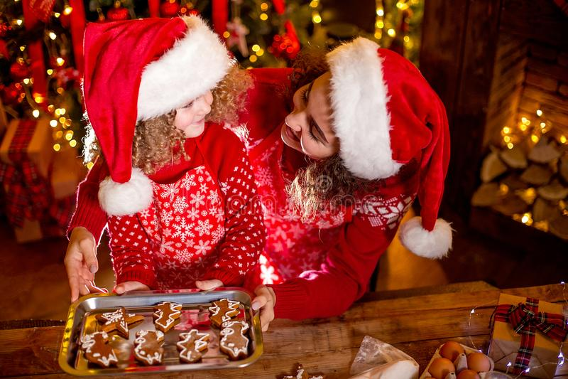 glada lyckliga ferier för jul Gladlynt gullig lockig liten flicka och hennes äldre syster, i att laga mat för santas hattar royaltyfria foton