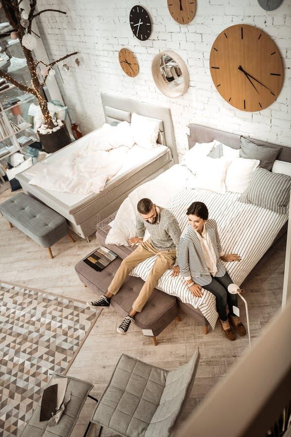 Glade aktiva par som kontrollerar softness av den framlade madrassen arkivbilder
