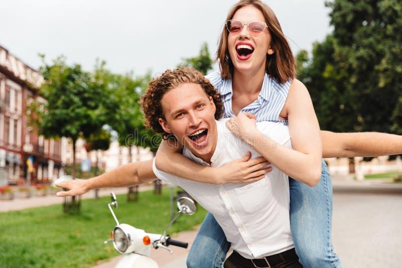 Glade barnpar som har gyckel samman med sparkcykeln royaltyfria bilder