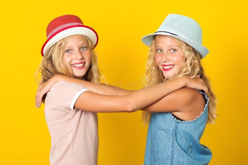 Glade flickor som bär sommarhatt, som ställer sig över gul bakgrund Ganska systrar som gnäller och ler Sommarmode glad arkivfoton