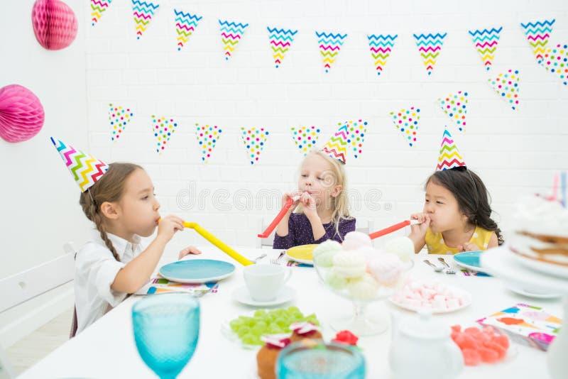 Glade flickor som blåser partihorn royaltyfri foto