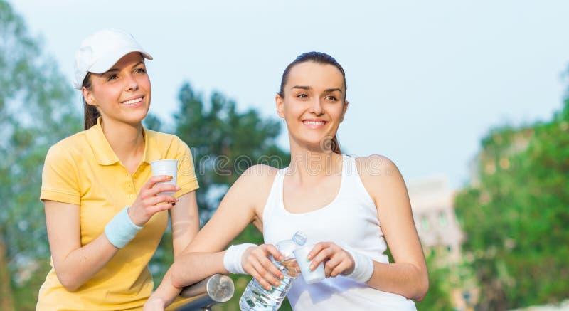Glade flickvänner i sportar som beklär dricksvatten royaltyfria bilder