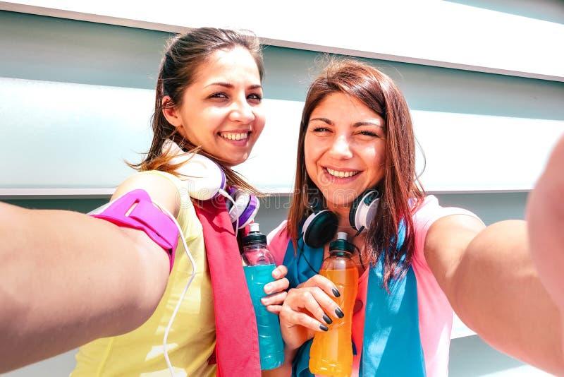 Glade flickvänner som tar selfie på rast i stadsmiljö - unga lyckliga kvinnor som har kul tillsammans royaltyfri foto