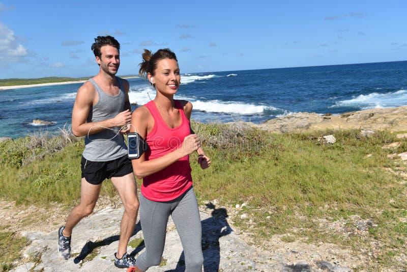 Glade joggers som kör på en härlig sommardag fotografering för bildbyråer