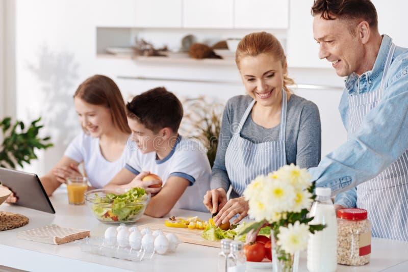 Glade lyckliga föräldrar som lagar mat matställen royaltyfria foton
