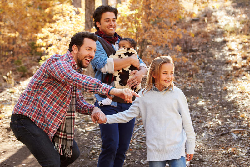 Glade manliga par med barn som går till och med nedgångskogsmark royaltyfri fotografi